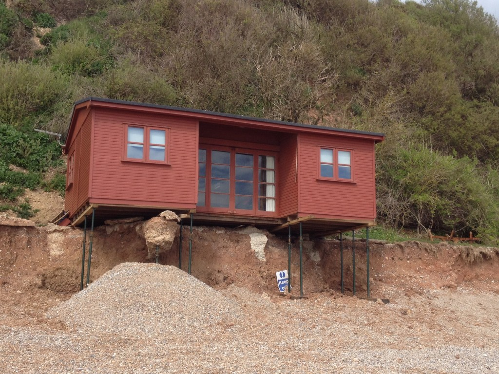 Storm damaged chalet on Branscombe beach