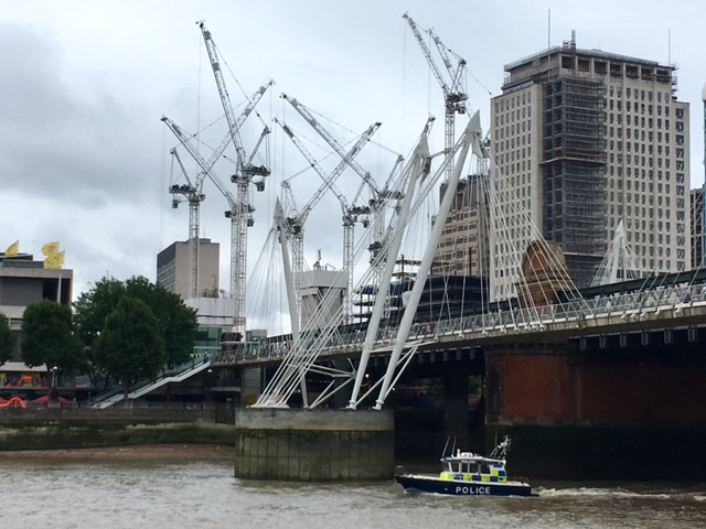 Cranes and a police boat, River Thames, London